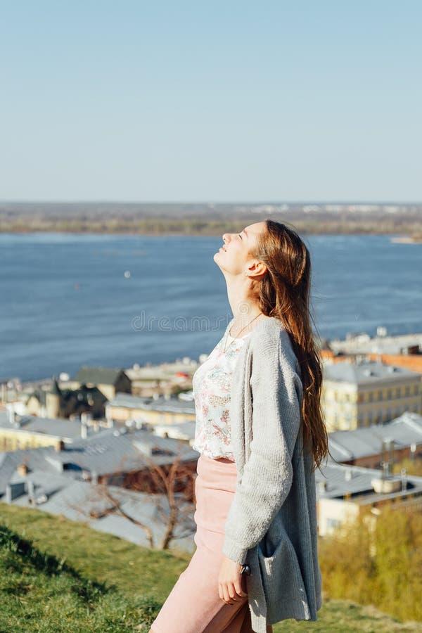 Мечтательная милая женщина сидя рекой города стоковое изображение rf