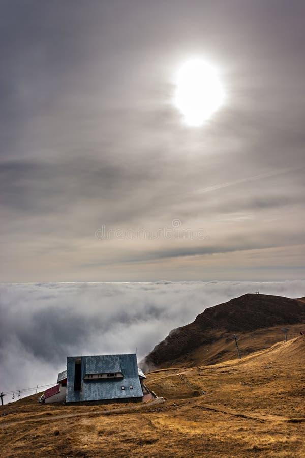 Мечтательная сцена горы с шале и крышка облаков на moun стоковое изображение rf