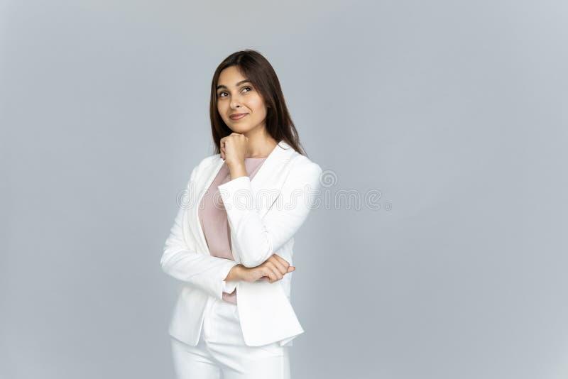Мечтательный индийский взгляд бизнес-леди на космосе экземпляра изолированном на серой предпосылке стоковое изображение