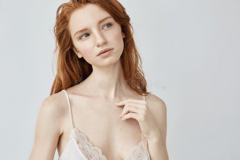 Мечтательная молодая девушка redhead при веснушки представляя думать стоковое фото