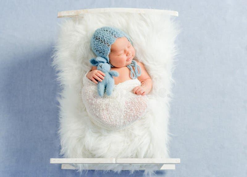 Мечтательные newborn сны игрушки удерживания мальчика стоковая фотография rf