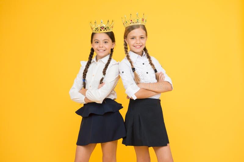 Мечтать о славе и богатстве Коронование награды Гениальные зрачки Школьницы носят золотой символ крон уважения стоковые фото