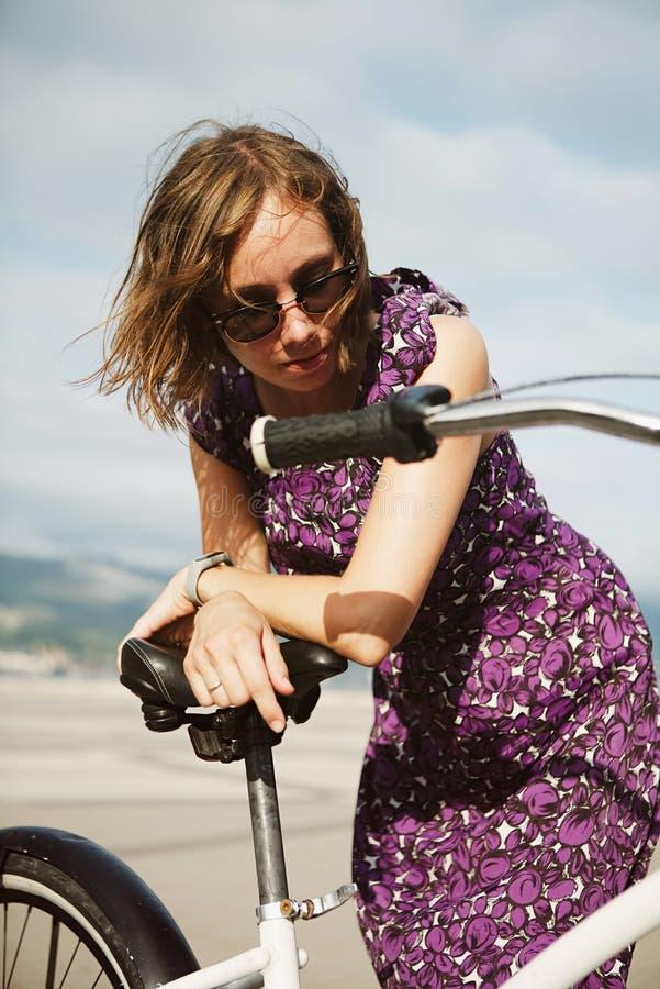 Мечтая девушка представляя с велосипедом стоковая фотография rf