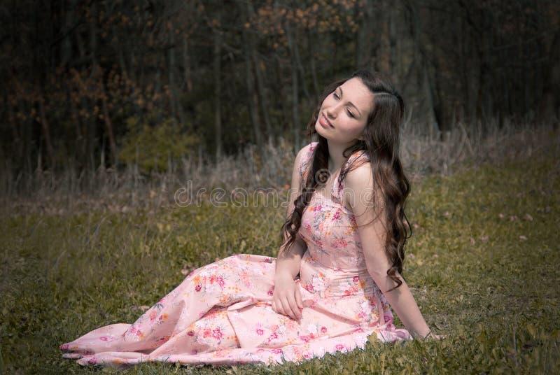 Мечтая девушка которая сидит на траве стоковое изображение rf