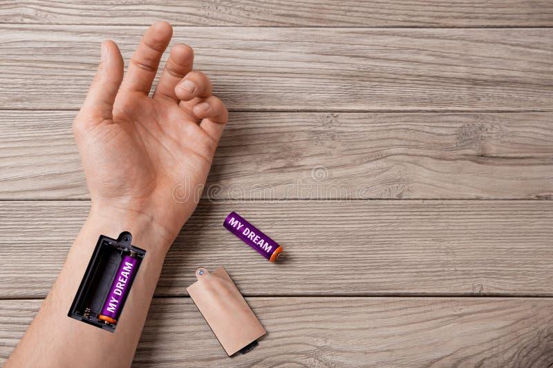 Мечта дает прочность и энергия двигает дальше Сформулируйте мою мечту пишет на батарее Рука человека с шлицем для поручая батарей стоковые изображения rf