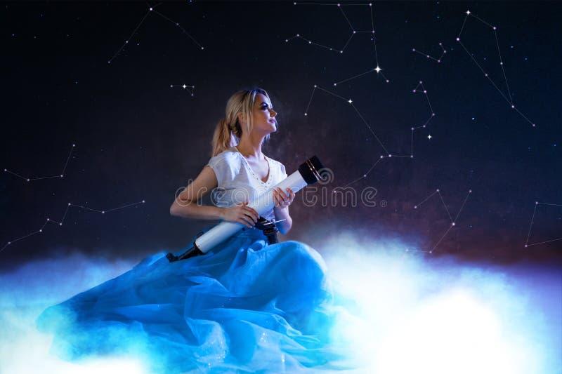 Мечты будущего, концепция молодой женщины Девушка над облаками смотрит вверх и использует телескоп небо звёздное стоковое изображение rf
