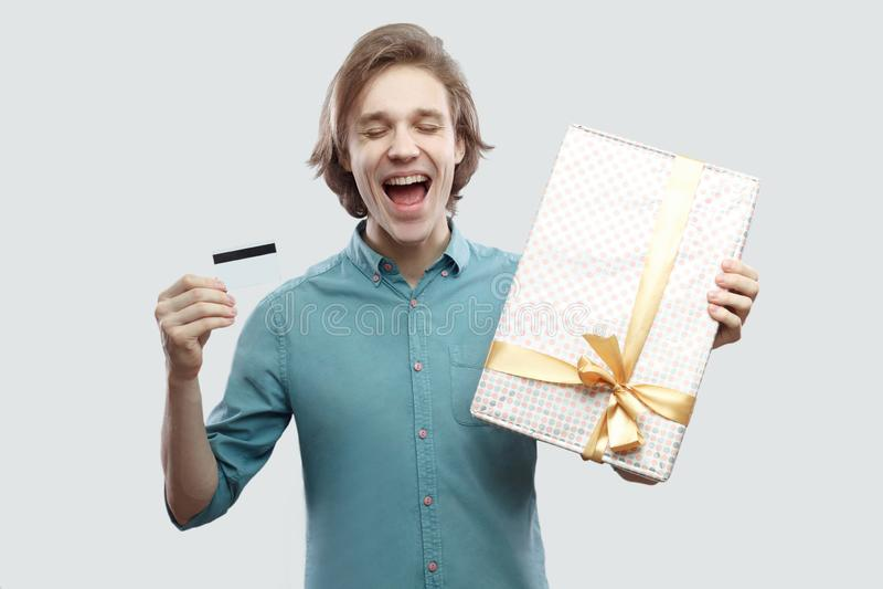 Мечты приходят истинный с онлайн покупками! Удовлетворенный молодой человек в светлом - голубые положение рубашки и настоящий мом стоковое фото