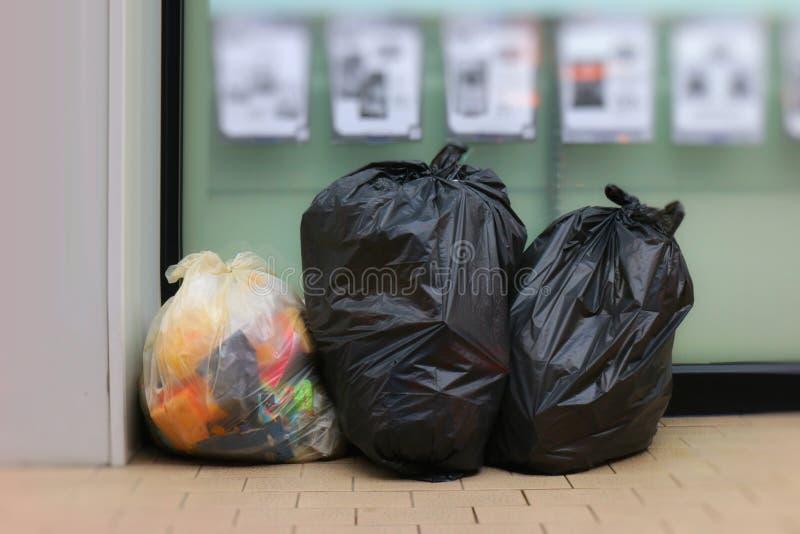 3 мешка для мусора, чернота сумки отброса установили передний ночной магазин, ящик, погань, мешок для мусора, погань на тротуаре, стоковое изображение rf