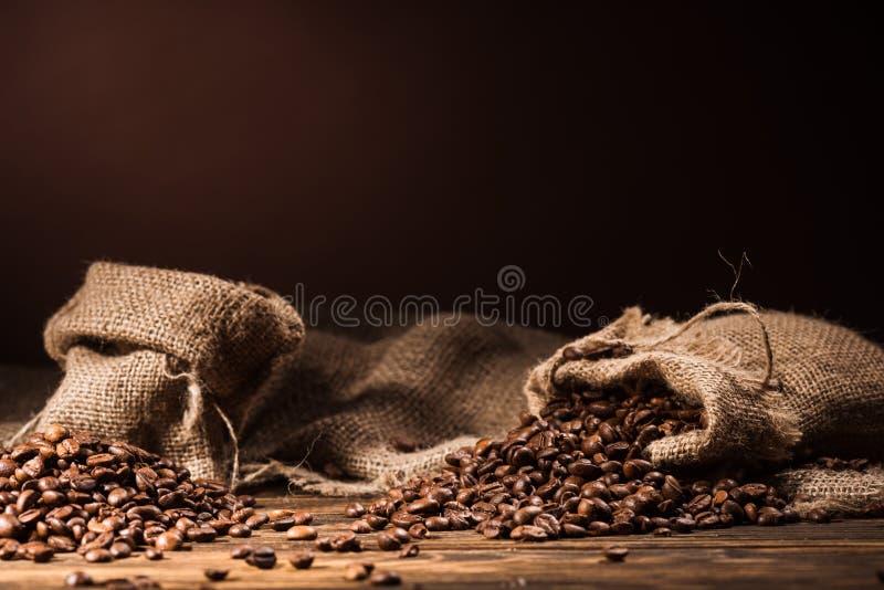 мешки кофейных зерен на деревенском деревянном столе на темноте стоковые изображения