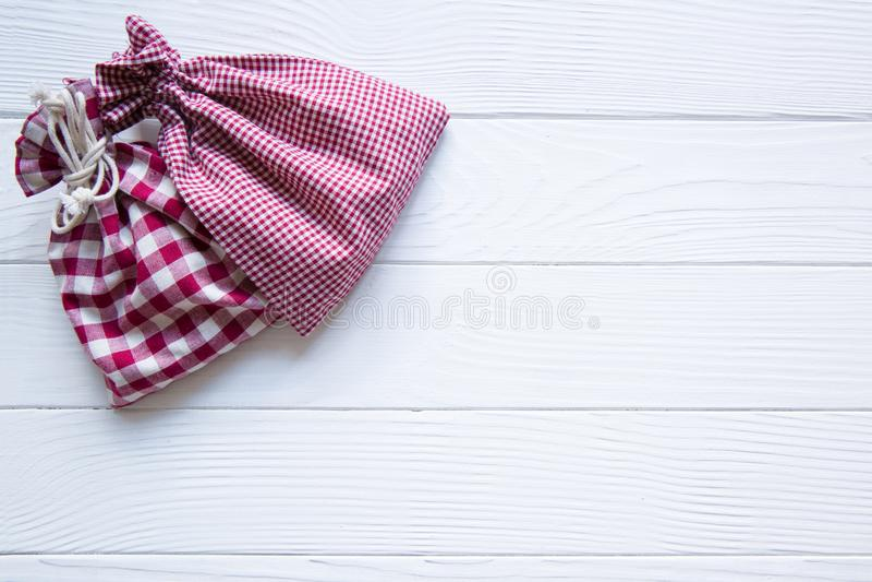 Мешки рождества красные chequered на белой деревянной деревенской предпосылке, стоковое фото