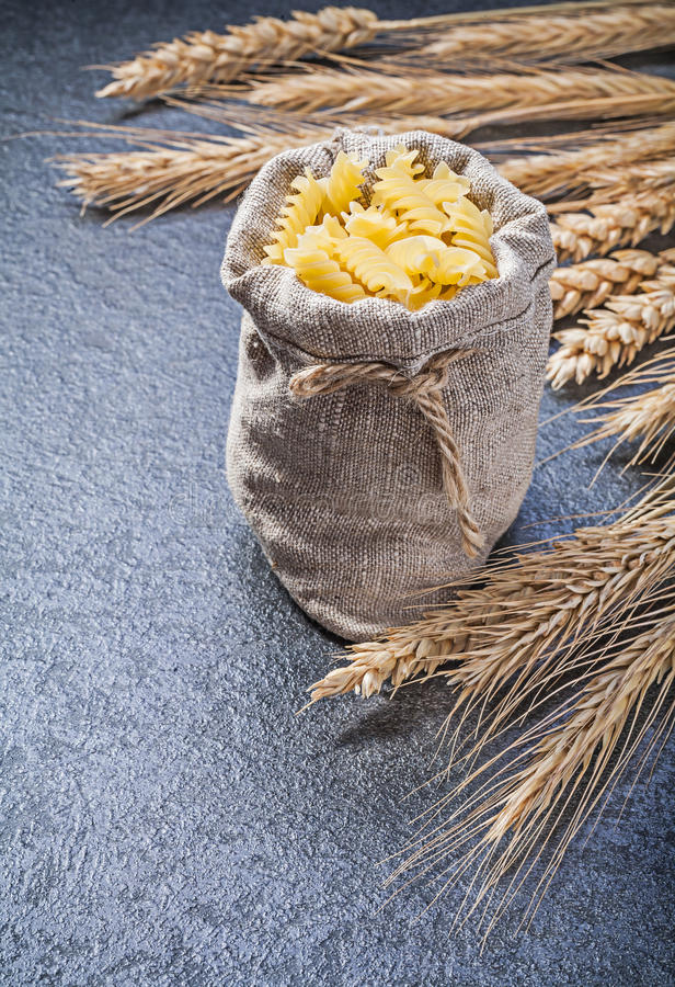 Мешок с ушами рож пшеницы спиральной макарон золотыми на черном backgro стоковая фотография rf