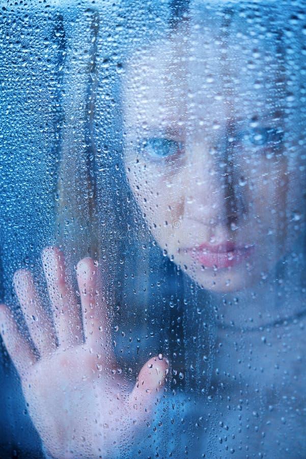 Меланхоличная и унылая молодая женщина на окне в дожде стоковое фото rf