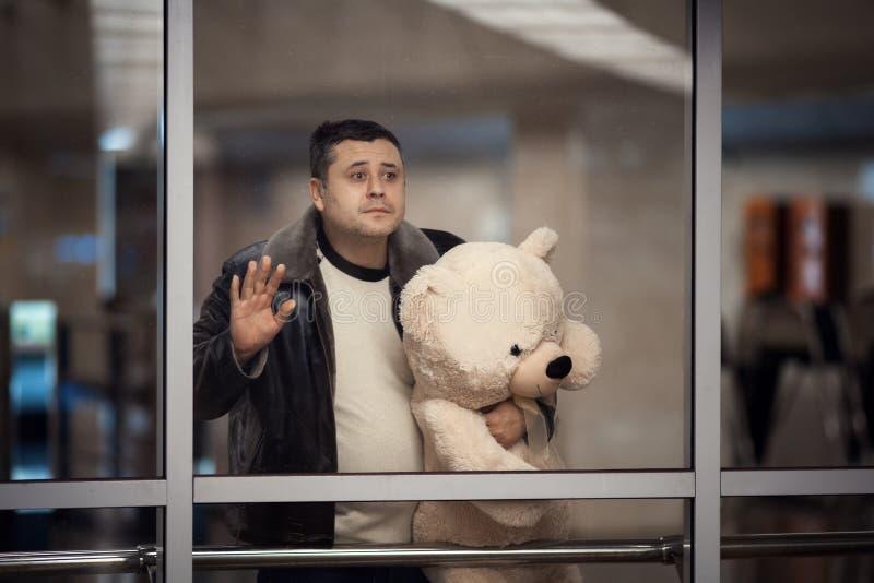 Медведь игрушки удерживания человека и смотреть уныло в расстояние стоковое фото rf