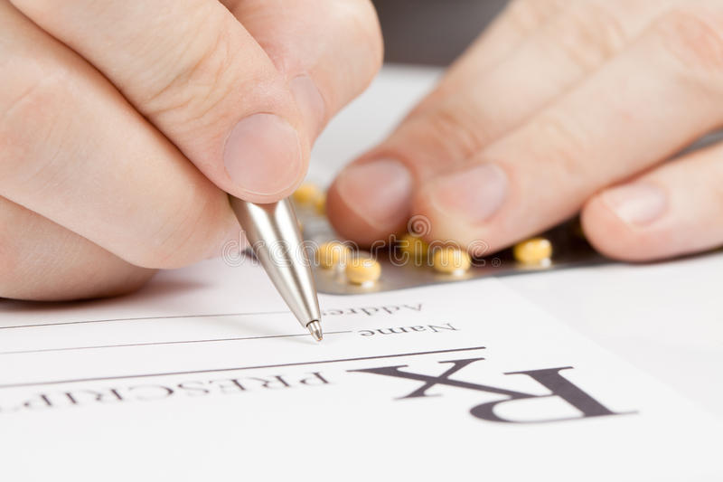 Медицина, здравоохранение и все вещи связали - врачуйте держать пилюльки с одной рукой и подписание рецепта с другими стоковое изображение