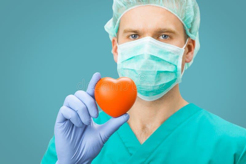 Медицина и здравоохранение - хирург в зеленом равномерном сердце игрушки удерживания на свете - голубая предпосылка стоковое фото