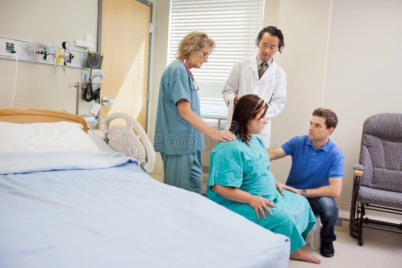 Медицинская бригада и человек смотря беременную женщину внутри стоковая фотография rf