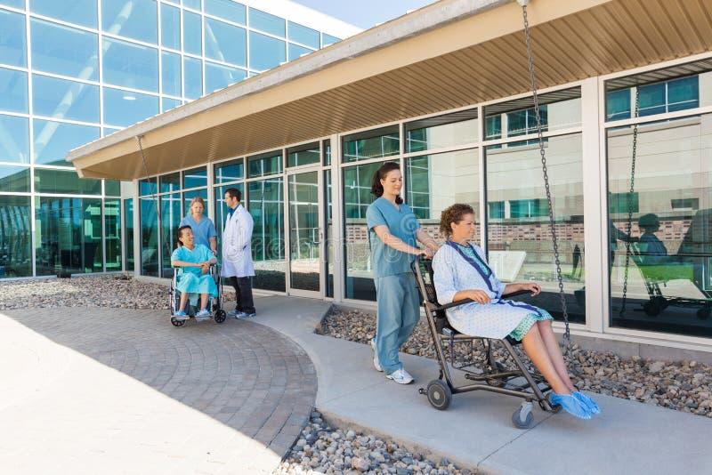 Медицинская бригада с пациентами на кресло-колясках на стоковая фотография