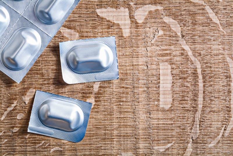 Медицинские пилюльки на деревянной доске стоковое изображение