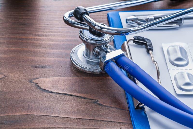 Медицинские пилюльки доски сзажимом для бумаги стетоскопа в пакете дальше стоковая фотография