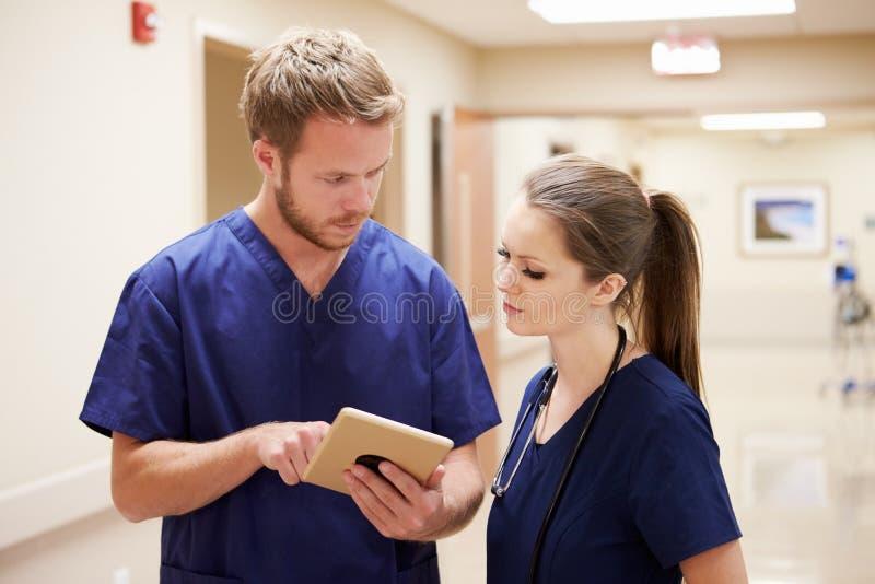 Медицинский персонал смотря таблетку цифров в коридоре больницы стоковая фотография rf