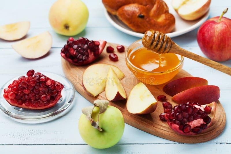 Мед, куски яблока, гранатовое дерево и hala на деревянной доске Таблица установила с традиционной едой на еврейский праздник Ново стоковая фотография