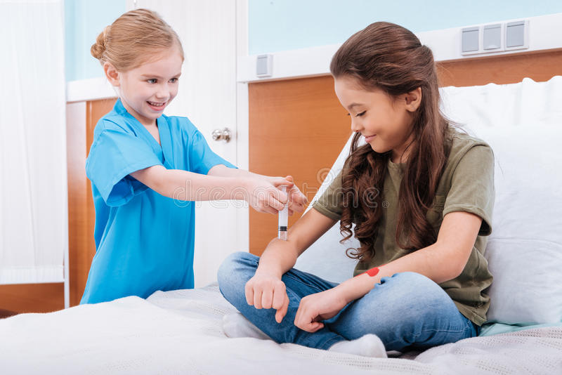 Медсестра девушки делая впрыску к усмехаясь пациенту в камере больницы стоковые фотографии rf