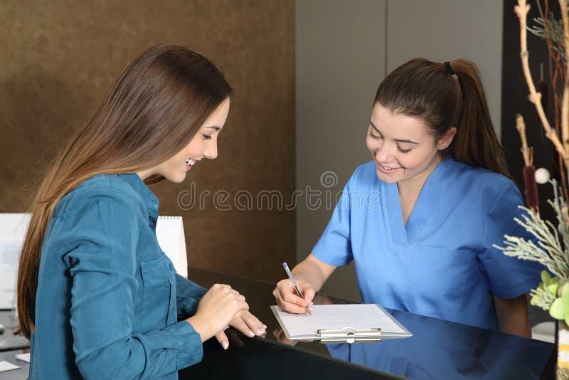 Медсестра или дантист присутствуя на клиенте стоковое изображение