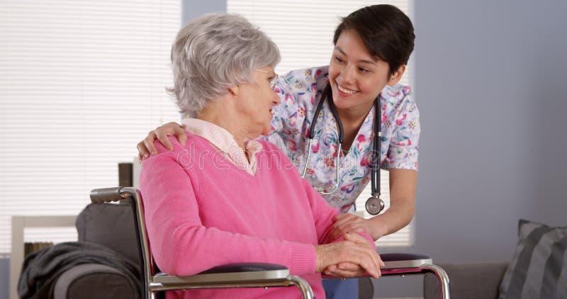 Медсестра китайца разговаривая с старшим пациентом стоковое изображение
