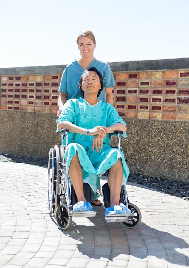 Медсестра нажимая расслабленного пациента на кресло-коляске на стоковые изображения rf