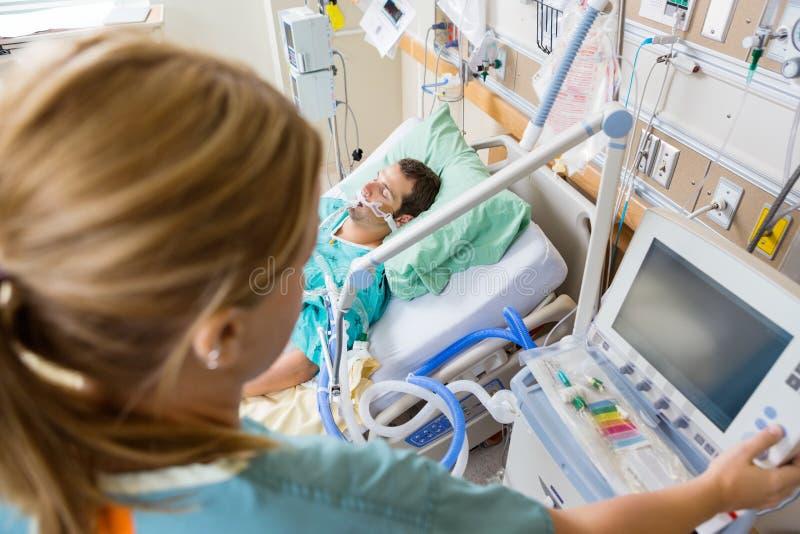 Медсестра отжимая кнопку монитора с терпеливый лежать стоковое фото