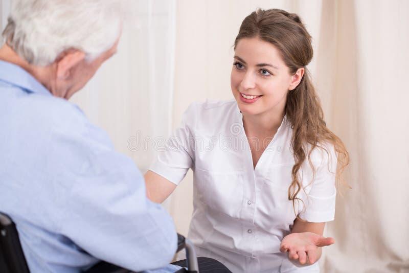 Медсестра разговаривая с старшим человеком стоковые изображения rf