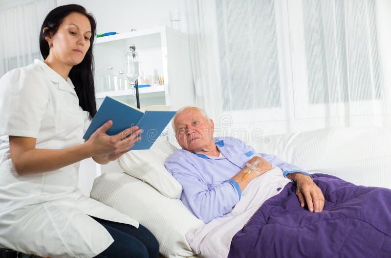 Медсестра читая книгу к его пациенту стоковые изображения rf