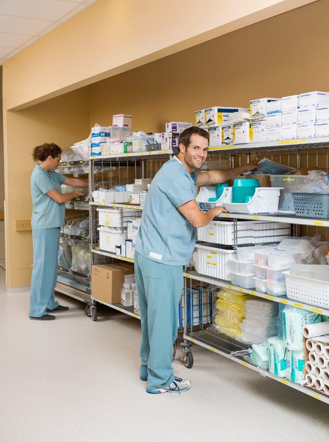 Медсестры аранжируя запас на полках в складском помещении стоковые фото