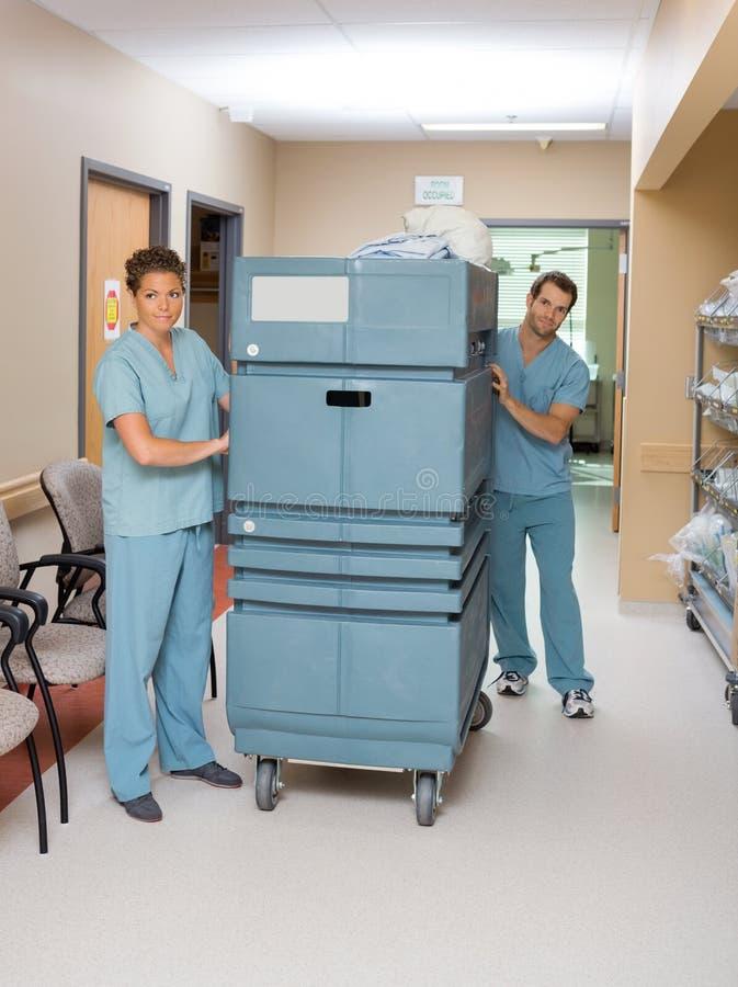Медсестры нажимая вагонетку в прихожей больницы стоковое фото rf