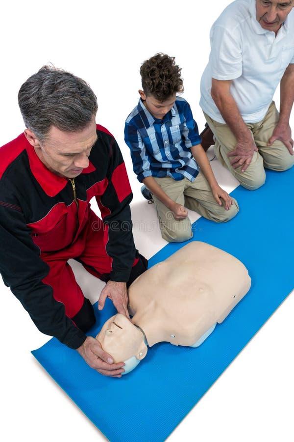 Медсотрудник тренируя кардиопульмональную реаниматологию к старшему человеку и мальчику стоковая фотография rf