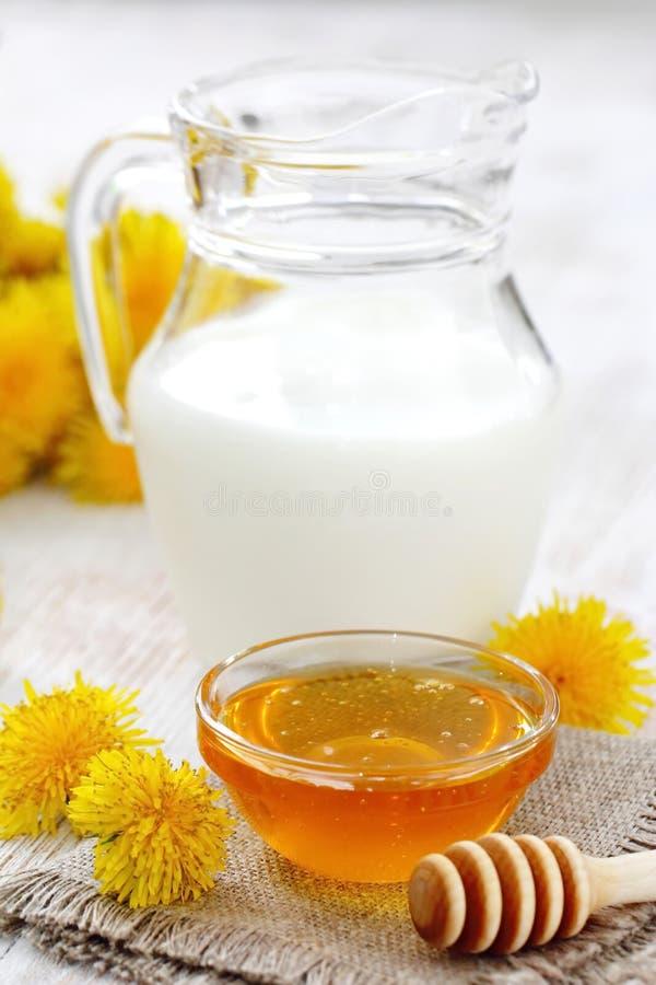 Мед цветка в стеклянном шаре и молоке стоковые изображения