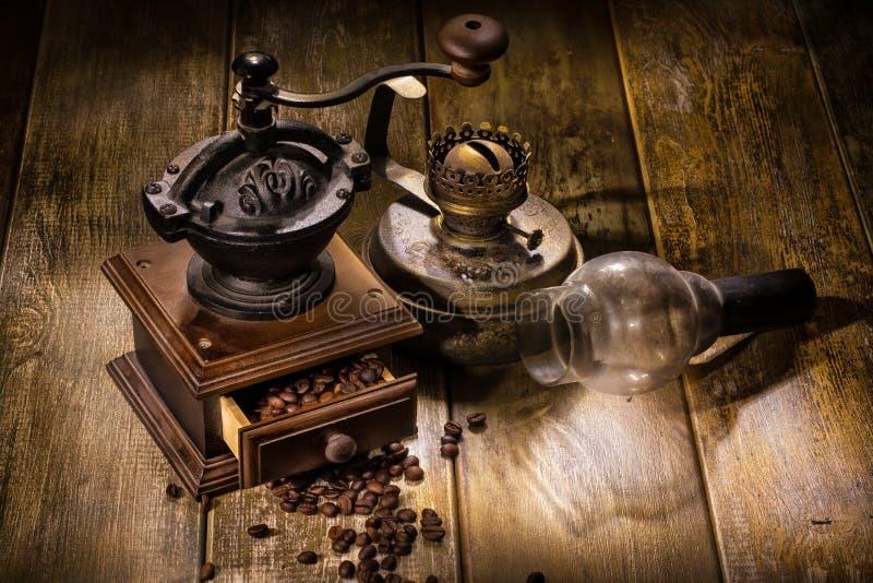 Мельница кофе и старая масляная лампа стоковое изображение