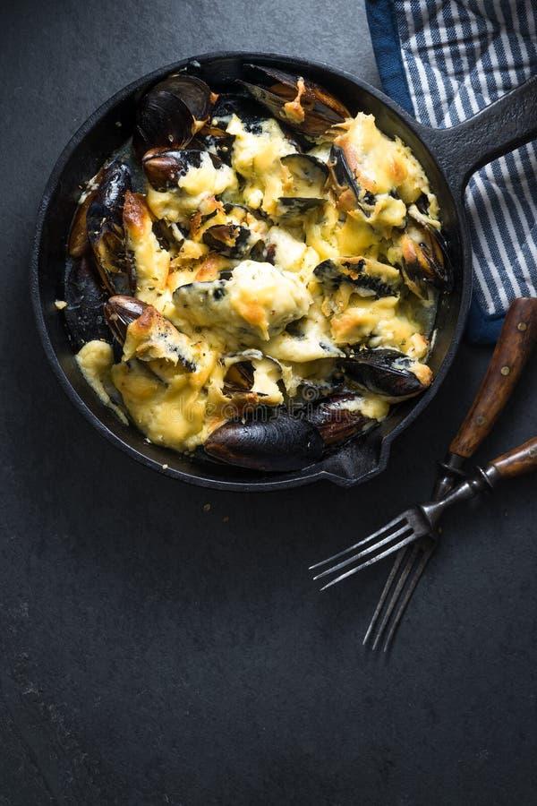 Мидии с соусом сыра в открытом космосе сковороды, салфетки и вилок стоковые фотографии rf