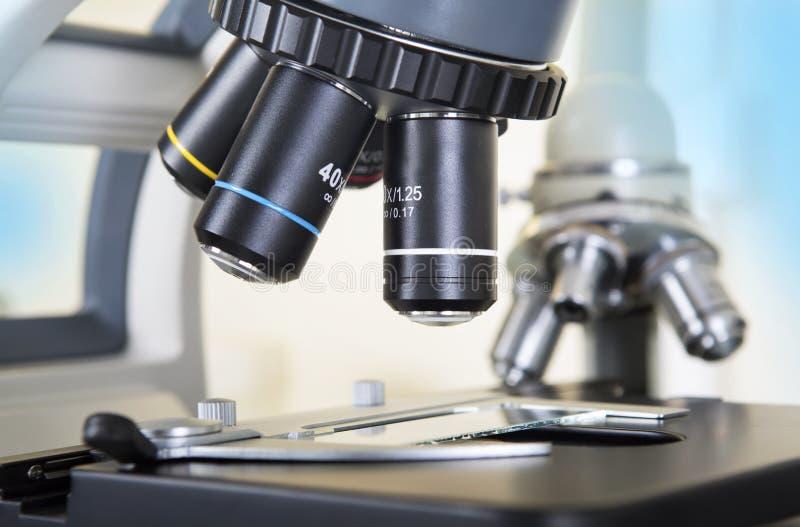 микроскоп лаборатории предпосылки над белизной Предпосылка научных и здравоохранения исследования стоковое изображение