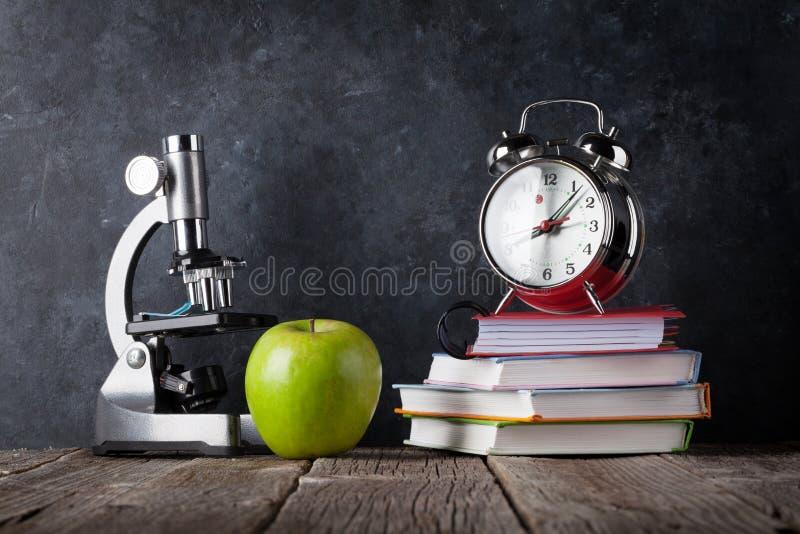 Микроскоп, будильник, книги и яблоко стоковые изображения rf