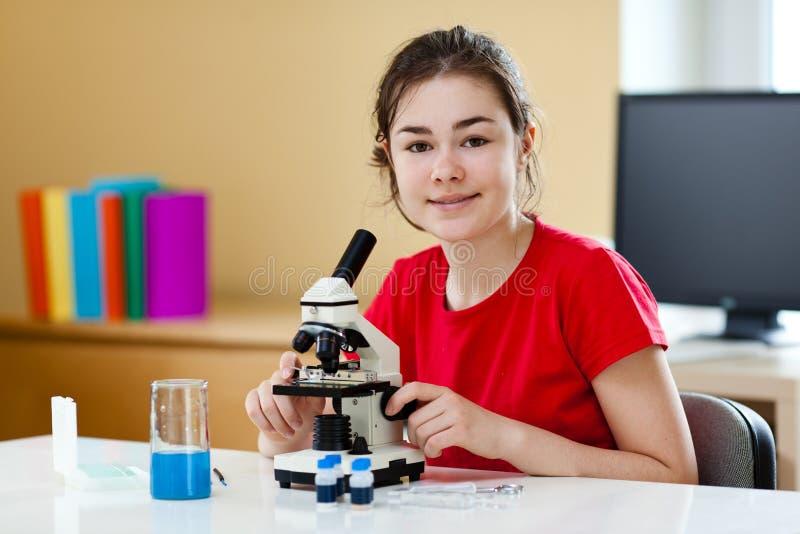 микроскоп девушки используя стоковое фото