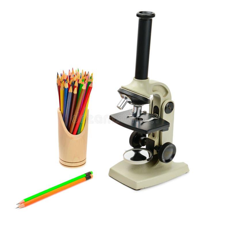 Микроскоп и карандаши лаборатории изолированные на белой предпосылке стоковая фотография rf