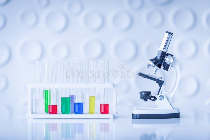 Микроскоп и красочные пробирки на таблице в лаборатории Scien стоковые фотографии rf