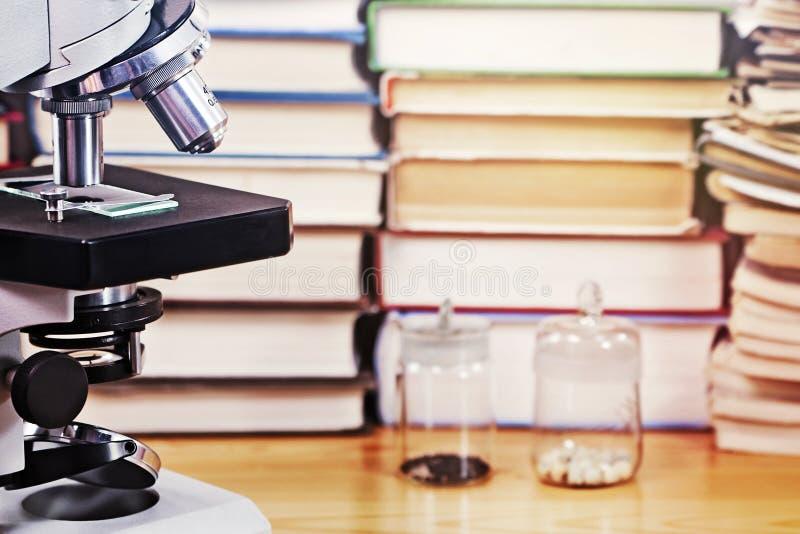 Микроскоп и много научных книг стоковые изображения rf