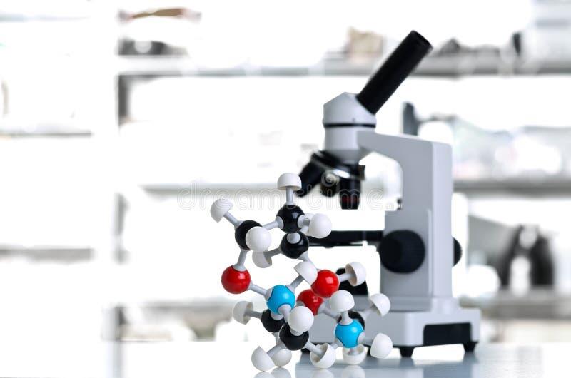 Микроскоп с моделью молекулы в лаборатории стоковая фотография