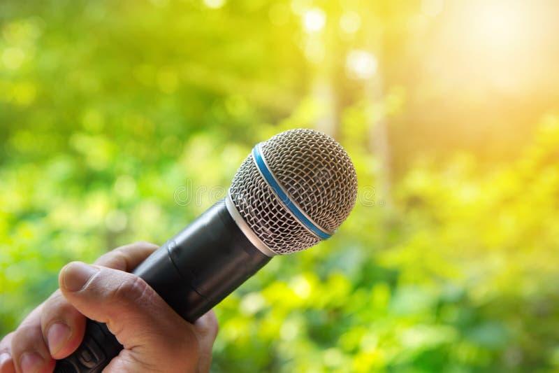 Микрофон в руке для петь или представлении с зеленым цветом природы стоковая фотография