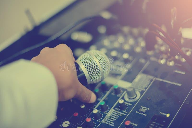 Микрофон в руке и отрегулировать аудио регулятор смесителя в c стоковое фото rf