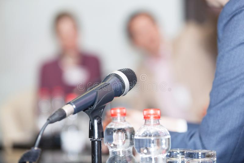 Микрофон в фокусе против запачканных людей на событии круглого стола стоковые изображения rf
