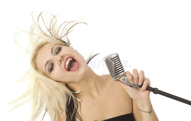 микрофон главным образом тряся белизну певицы стоковые фото