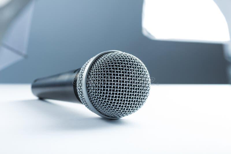 Микрофон лежа на белой таблице На фоне оборудования студии, освещение стоковое изображение